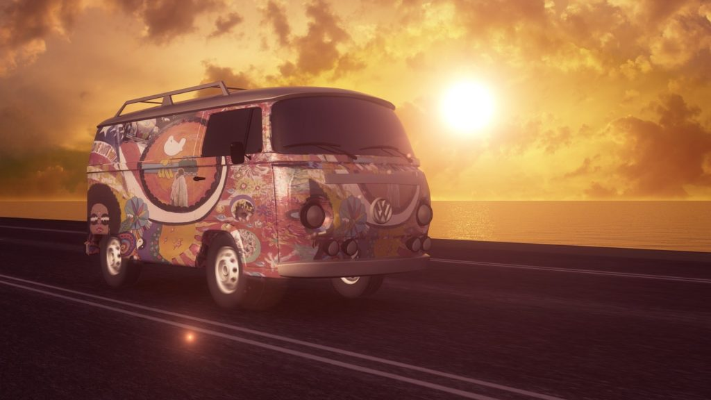 Psychedelic hippie VW van driving at sunset