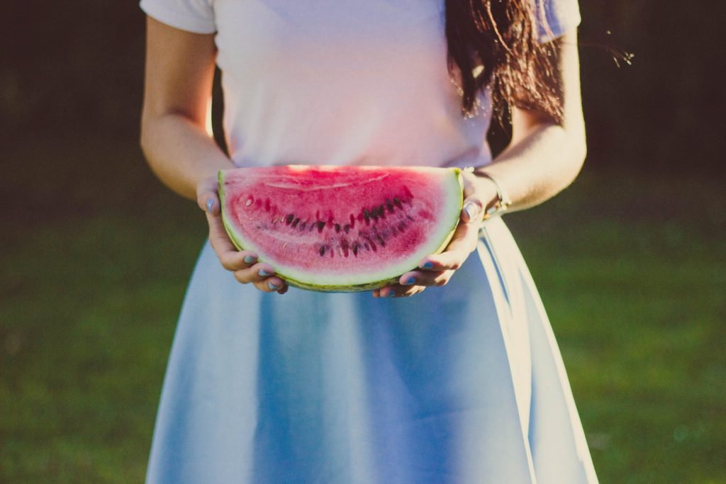 Woman holding a slice of watermelon outdoors