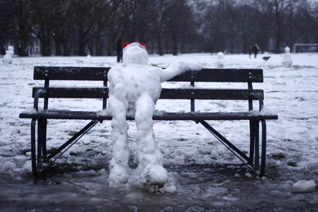 Melting snowman with Santa hat sitting on a bench